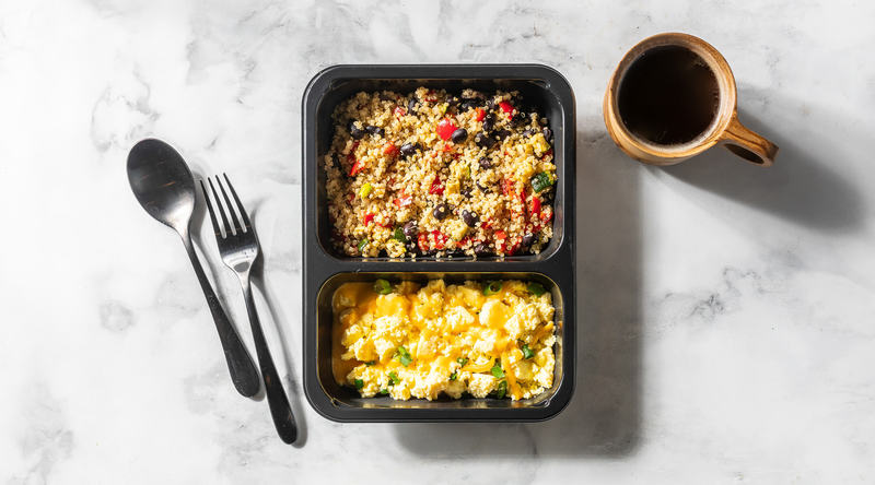 Scrambled eggs and quinoa with veggies, shown in their microwave-friendly tray from Factor, with silverware and a cup of coffee.